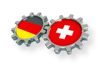 Zahnräder aus Deutschland und der Schweiz greifen ineinander